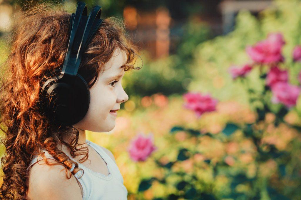 Ein kleines Mädchen mit roten Locken und Kopfhörern lächelt während sie ihre persönliche Meditation anhört. Im Hintergrund blühen Rosen.